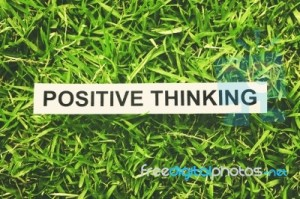 banner across grass that says positive thinking