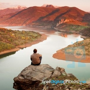 man sitting on a rock above a lake