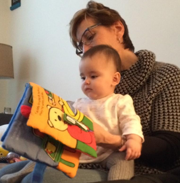 baby reading on Grandma's lap
