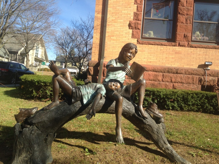statue of girl and boy with book