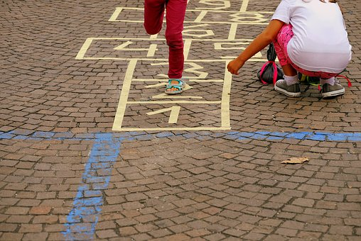 two children playing hopscotch